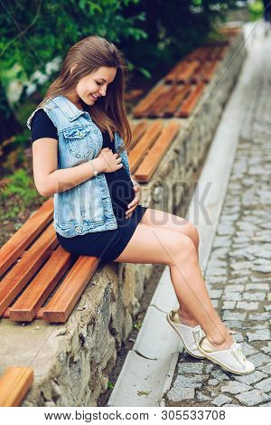 Beautiful Pregnant Woman In A Black Tight Dress And Blue Jeans Jaket Sitting On The Branch And Touch