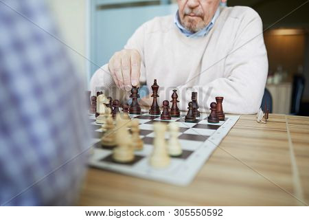 Aged Experienced Professional Grandmaster With Grey Beard Playing Chess With Opponent In Checked Shi