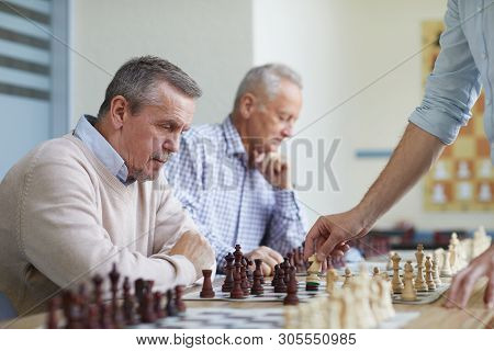 Two Aged Men With Silver Hair Spending Leisure Time At Chess Club By Playing Chess With Local Grandm