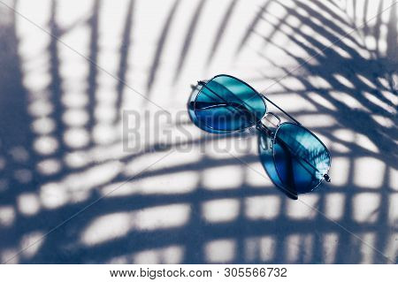 Stylish Blue Sunglasses On A Tropical Background With The Shadow Of Palm Leaves. Resort Recreation C