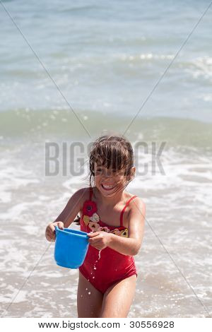 Little Girl Playing With A Bucket On The Beach