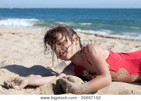 Little Girl Relaxing On The Beach Covered In Sand