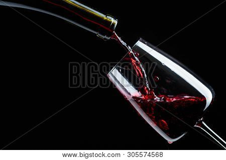 Red Wine Being Poured Into Wine Glass  On A Black Background.