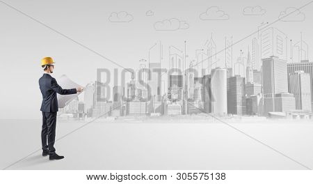Young supervisor architect standing and replanning a big city panorama poster
