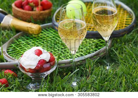 Enjoing In Wimbledon Tennis Championship With Champagne And Strawberries With Cream. Wimbledon Symbo