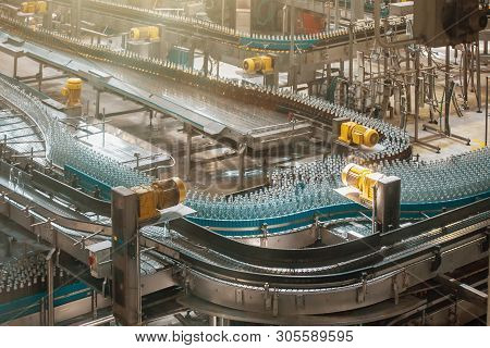 Automatic Conveyor Line Or Belt With Glass Bottles At Brewery Production. Industrial Beer Bottling E