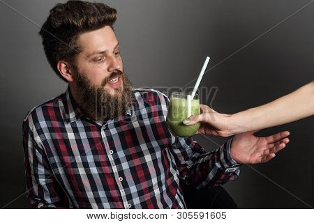 Young Man Looks Incredulously At Woman Giving Him Healthy Eating Green Spinach Smoothie