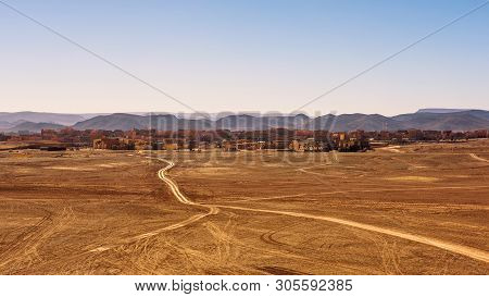Dirt Road Going To The City Of Ouarzazate In Morocco. Ouarzazate With Typical Moroccan Architecture