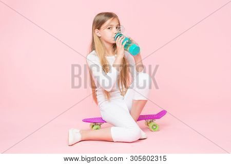 Water gives her energy. Little girl skater drinking water on pink background. Thirsty child drinking fresh water from plastic bottle. Little girl having a drink from water bottle sitting on penny board. poster