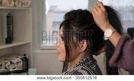 Stylish Pan-asian In Beauty Salon. Hands Of Hairdresser Hold Hair Of Client. Hairdressing Services.