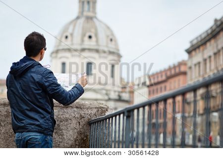 Portrait of a handsome, young, male tourist in Rome, Italy (dome of the Santissimo Nome di Maria church in the background)