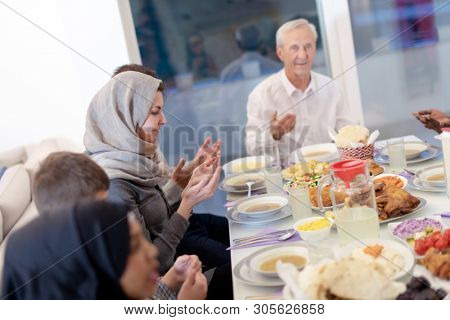 modern multiethnic muslim family praying before having iftar dinner together during a ramadan feast at home