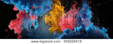 Acrylic blue and red colors in water. Ink blot. Abstract black background. Horizontal long banner.
