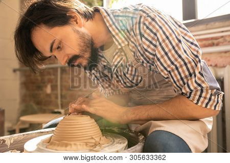 Young creative artisan bending over rotating clay item on wheel while using one of handtools for cutting and ornamenting