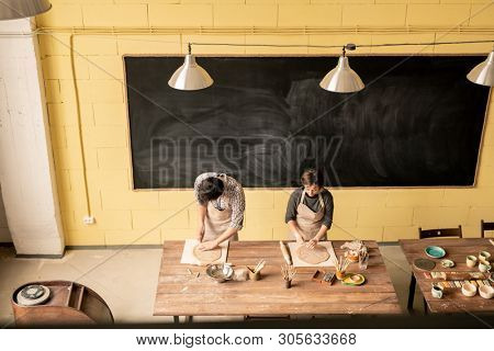 Two self-employed craftspersons working with rolled out clay while standing by wooden table in their workshop