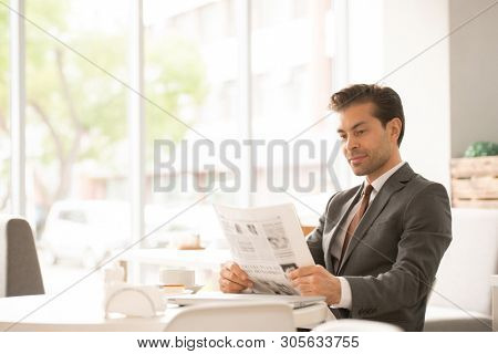 Young broker in formalwear sitting by table in cafe, holding newspaper in front of him and reading latest news in the morning
