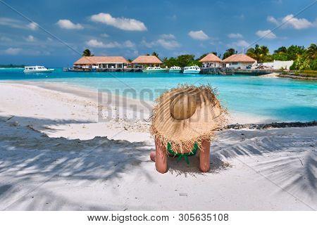 Woman sitting on beach under palm tree. Summer vacation at Maldives.