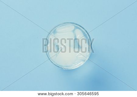 Refreshing cold Water with ice in a glass on a blue background. Concept of thirst, heat, refreshment in the summer. Flat lay, top view poster