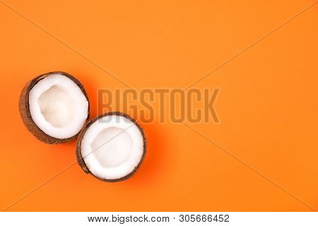 Top View Of Haved Ripe Coconut On Russet Orange Background. Summer Concept.  Minimal Flat Lay.place