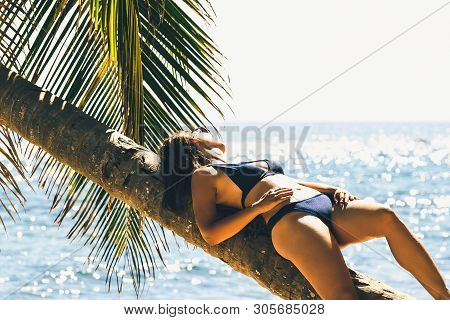 Traveler girl relaxing on tropical beach. Young girl traveler relaxing in vacation. Traveler relaxing on tropical beach in vacation. Girl in vacation relaxes on beach in summer day. Traveler. Summer. Vacations.