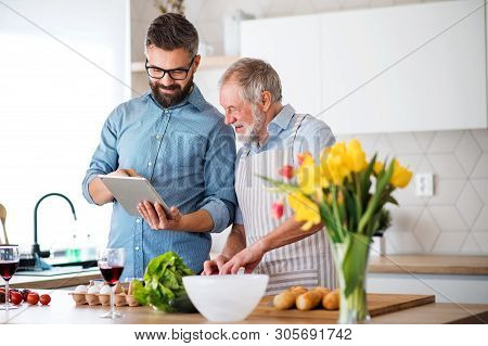 Adult Hipster Son And Senior Father Indoors In Kitchen At Home, Using Tablet.