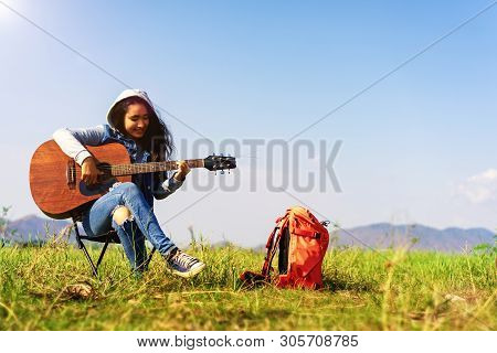 Beautiful Girl Sitting On A Chair And Playing A Guitar Beside The Orange Backpack.