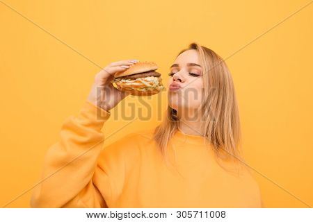 Pretty Girl In Yellow Clothes Holds A Burger And Kisses. Portrait Of A Hungry Girl On A Yellow Backg