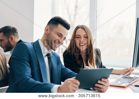 Smiling Successful Business People Discussing Ideas Using Digital Tablet In The Modern Office