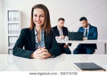Happy Smiling Business Woman Portrait Sitting In Office With Her Business Team On Background. Leader