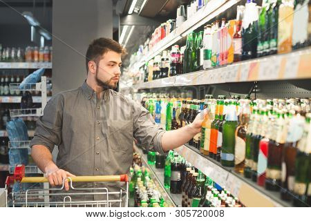Man With A Beard Buys A Beer In A Supermarket, Takes A Bottle From A Shelf In The Alcohol Department