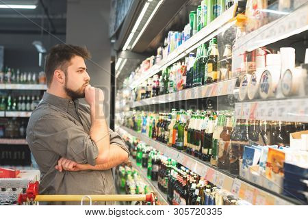 Thoughtful Man With A Beard Looks At Bottles With Beer In A Supermarket. Man Wears A Shirt, Looks At
