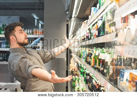 Funny Adult Looks At The Shelf With Bottles Of Beer And Can Not Choose, He Wants To Take Everything.