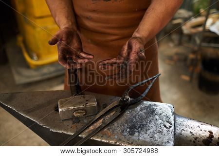 Close-up of unrecognizable blacksmith in apron standing at anvil with tongs and hammer and showing dirty hands after work poster