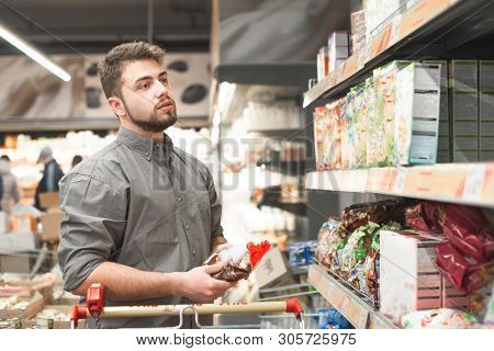 Man With A Beard Stands In A Supermarket With A Pack In His Hands And Looks At A Shelf With Flakes.