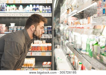Man With A Beard Looks At Bottles Of Milk Products In A Supermarket. Adult Man Chooses Milk On The G