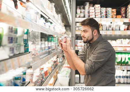 Funny Man With A Beard Is In The Milk Department Of The Supermarket Near The Shelves Of Yogurt, Hold