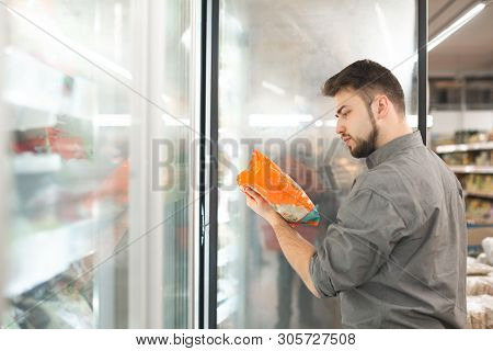 Buyer Standing In The Supermarket Near The Refrigerator Holds The Package In His Hand And Reads The