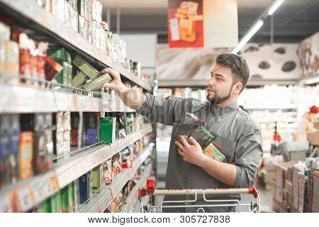 Buyer Buys A Discount Product At A Supermarket. Portrait Of A Man Wearing A Shirt, Takes Packets Of