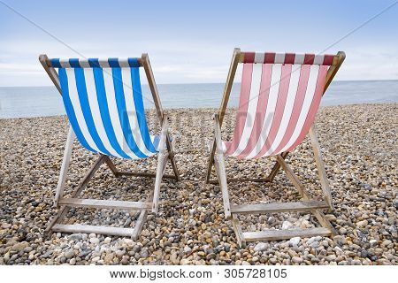Deckchairs On Beach, Typical English Seaside Holiday Scene, Red And Blue Stripes Representing Main P