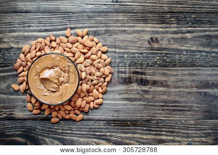 Whole Fresh Almonds With A Bowl Of Freshly Ground Creamy Almond Butter Over A Rustic Table Or Backgr