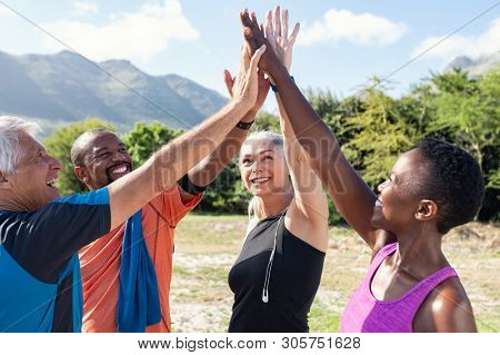 Happy fitness multiethnic class giving high five after completing exercise session. Group of sweaty mature men and sporty women giving high five and looking up. Smiling friends celebrate success.