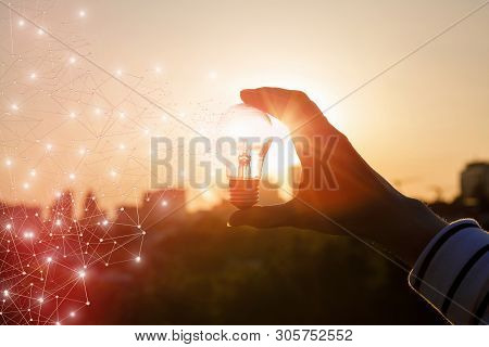 The Concept Of The Emergence Of Innovative Idea . Hand With Light Bulb At Sunset.