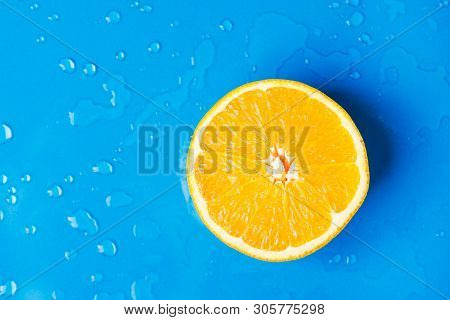 Raw Juicy Citrus Fruit Cut In Half Orange On Wet Blue Background With Water Drops Splashes. Summer B