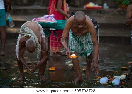 VARANASI, INDIA - MAR 23, 2018: Pilgrims plunge into the water holy Ganges river in the early morning. According to legends, the city was founded by God Shiva about 5000 years ago.