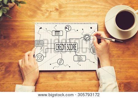 Credit Score Theme With A Person Writing In A Notebook On A Wooden Table