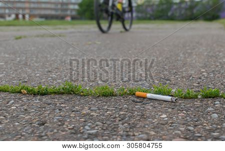 thrown Smoking cigarette butt lie on the asphalt path against the background of a passing bike poster