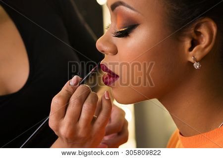 Makeup Artist Working With African American Model In Beauty Salon. Perfect Skin Facial. Beautiful Fa