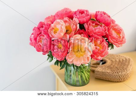 Coral Peonies In A Glass Vase And Wicker Bag On Wooden Table.. Beautiful Peony Flower For Catalog Or