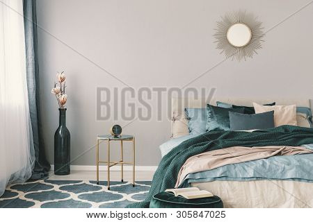 Flowers In Stylish Bottle Like Vase Next To Trendy Nightstand With Clock In Beautiful Bedroom Interi