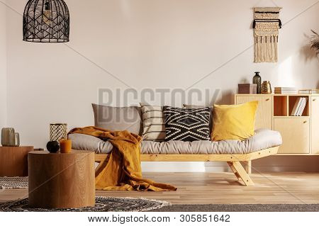 Scandinavian Sofa With Pillows And Dark Yellow Blanket In Bright Living Room Interior With Black Cha